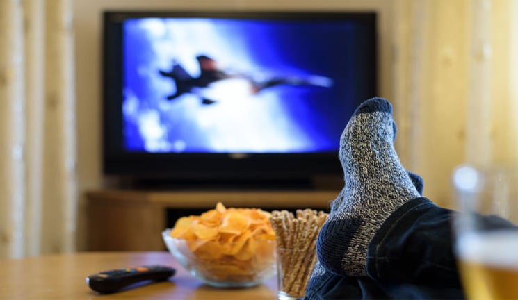 watching TV war movie (military jet) with feet on table, eating snacks